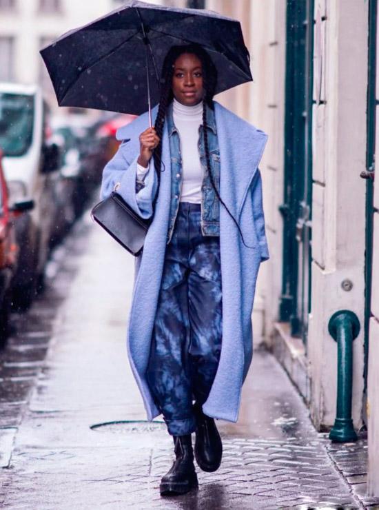 Девушка в свободных брюках, джинсовка и длинное голубое пальто тедди, образ дополняют черные ботинки на шнуровке и зонт