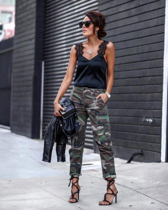 Девушка в свободных брюках хаки, черный шелковый топ и босоножки