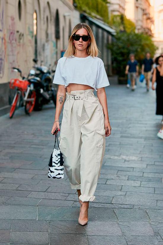 Девушка в свободных брюках, укороченная футболка и туфли