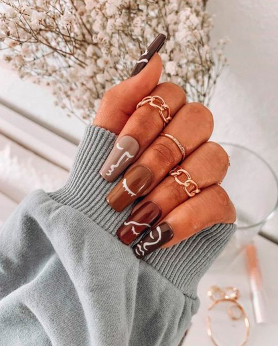 Длинные коричневые ногти с белый принтом