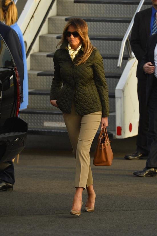 Мелания Трамп в стеганой куртке и серых брюках