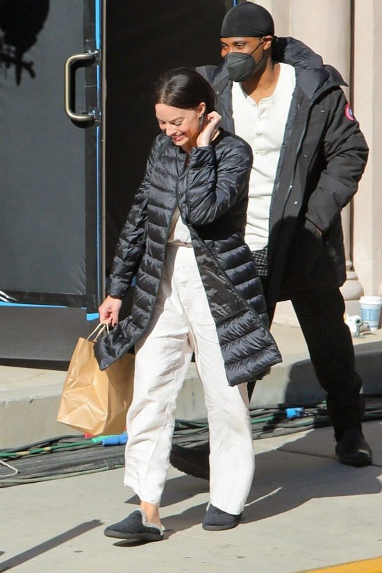 Марго Робби в белых брюках и пуховике