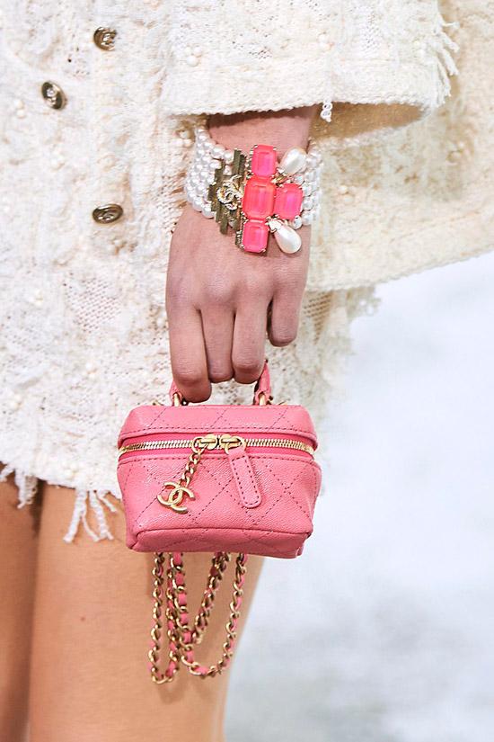 Модель с розовой мини сумочкой на молнии с золотыми цепочками от chanel