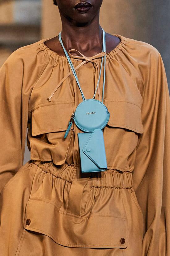 Модель в бежевом платье на резинке с карманами, образ дополняет голубая сумочка мини на шее от max mara