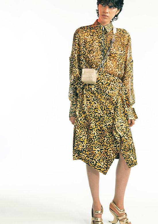 Модель в черно золотом платье миди с длинными рукавами, золотые босоножки и бежевая мини сумочка от givenchy