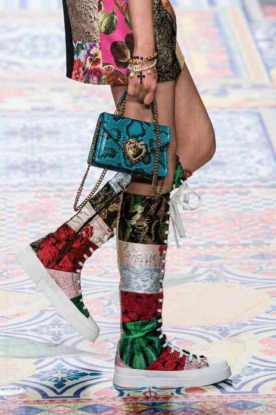 Модель в необычных разноцветных сапогах на шнуровке, голубая мини сумочка из змеинной кожи с золотыми цепочками от Dolce & Gabbana