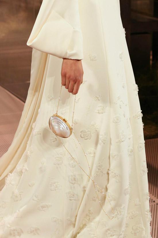 Модель в широком белом платье в пол и с маленькой овальной сумочкой с тонкой золотой цепочкой от fendi