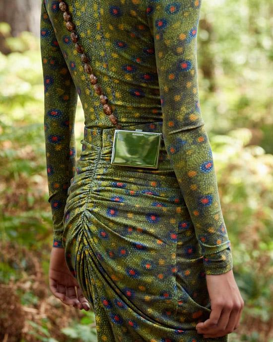 Модель в зеленом обтягивающем платье с длинными рукавами и глянцевой мини сумкой на поясе от burberry