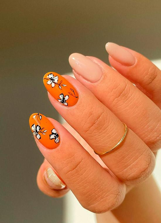 Оранжевый маникюр с черно белыми цветами на овальных ногтях