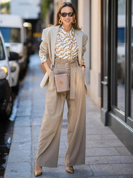 Девушка в широких брюках палаццо, светлая блузка с принтом и бежевый блейзер, образ дополняют туфли на шпильке и солнцезащитные очки