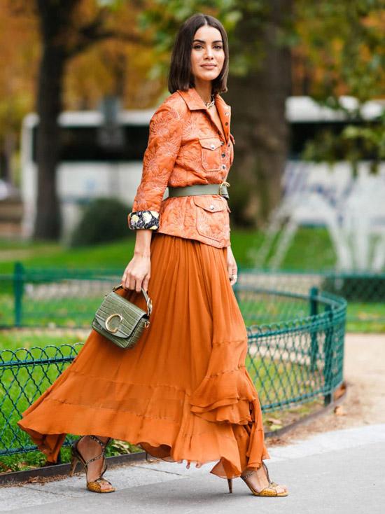 Девушка в воздушной юбке макси с воланами, оранжевый блейзер с ремнем на талии, образ дополняют босоножки на шпильке и серая мини сумочка