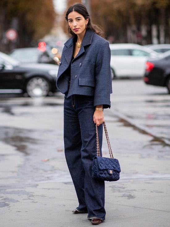 Девушка в темно синих прямых джинсах, серый укороченный жакет и сумочка