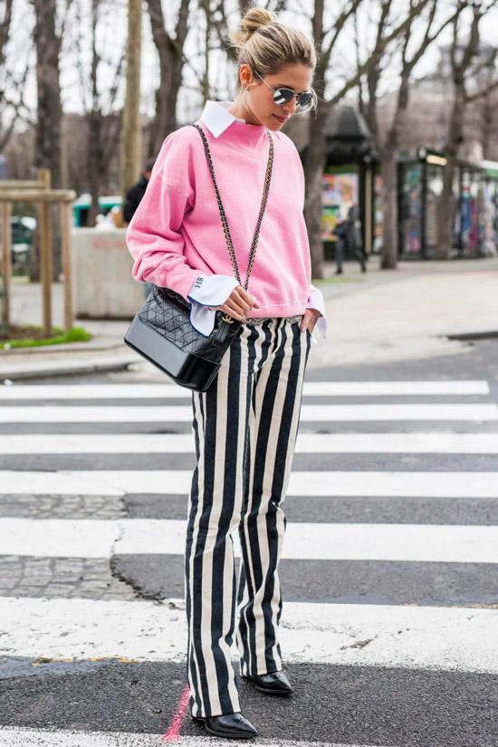 Девушка в черно белых брюках в вертикальную полоску, нежно розовый свитер и темная сумка, образ завершают черные туфли на шпильке