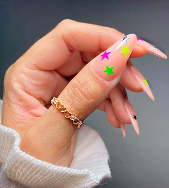 Бежевый маникюр с неоновыми звездами на длинных острых ногтях