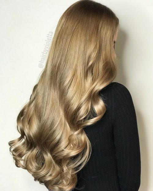 Девушка с длинными гладкими волосами с теплым золотистым блеском