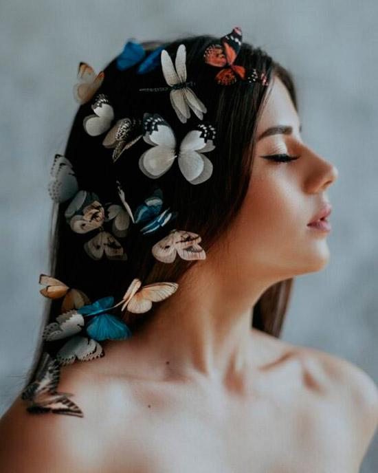 Девушка с естественным макияжем, распущенные волосы украшены бабочками