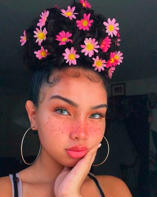 Девушка с милым розовым макияжем с веснушками и нежными розовыми цветами в волосах