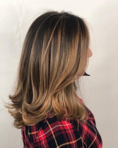 Девушка с натуральными темными волосами с более светлыми прядями