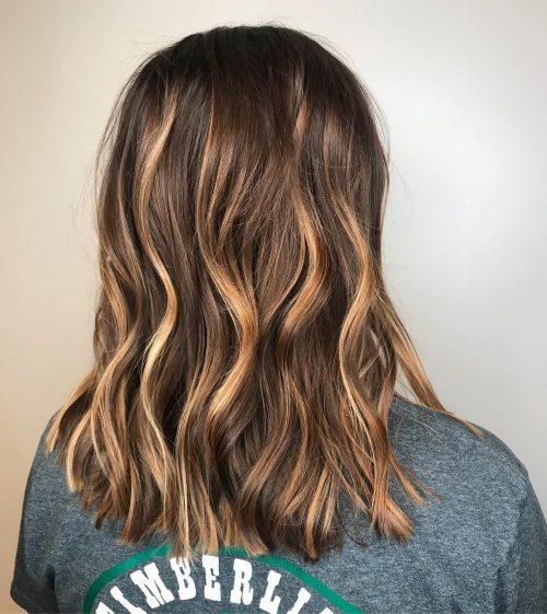Девушка с темными натуральными волосами со светлыми прядями, волосы средней длины