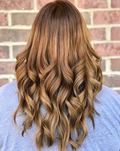 Девушка с волосами карамельного цвета с легкими локонами