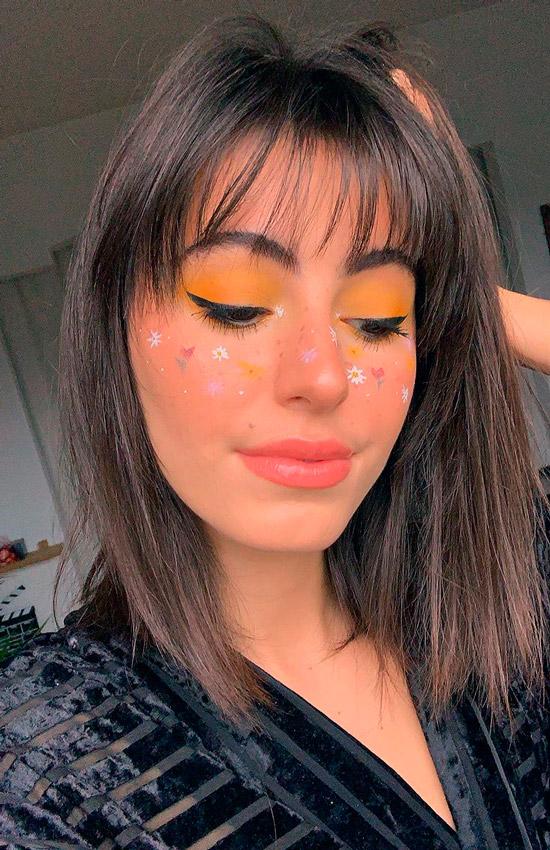 Девушка с желтым макияжем глаз, светлая помада, ухоженные волосы с тонкой челкой