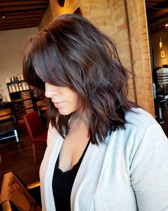 Девушка со стильной стрижкой миди на темных волосах с легкими волнами и челкой