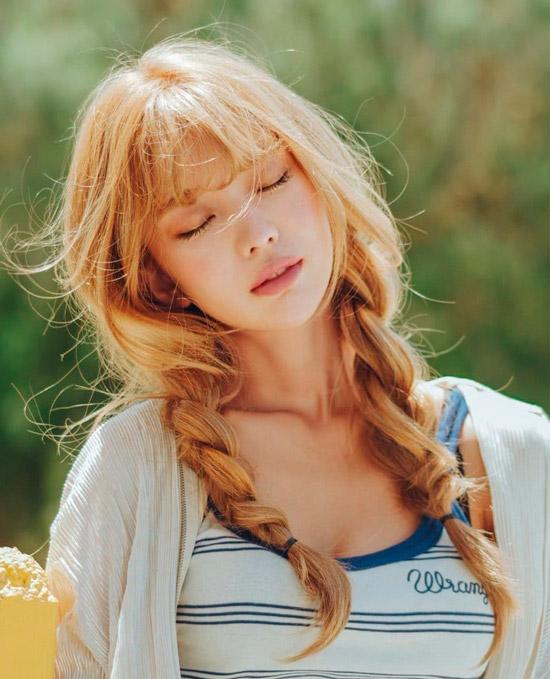 Девушка со светлыми рыжими волосами заплетенные в свободные косички и челка