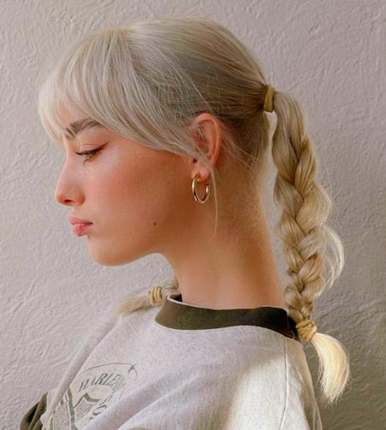 Девушка со светлыми волосами заплетенные в две косички с удлиненной челкой