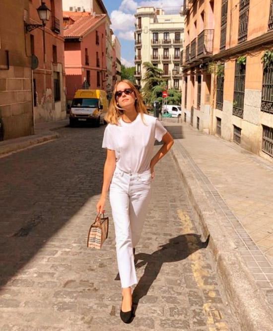 Девушка в белых джинсах, простая футболка и черные балетки, образ завершают солнцезащитные очки
