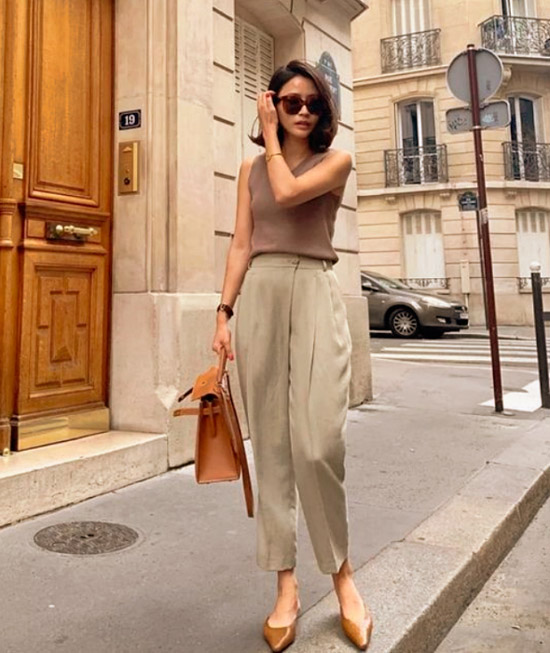 Девушка в бежевых брюках, простой топ и коричневые туфли на плоской подошве