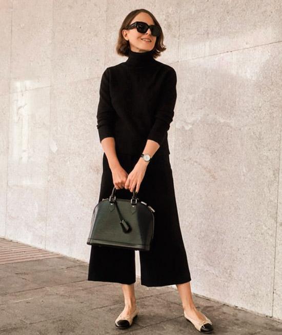 Девушка в черном свитере, брюки кюлоты и балетки на плоской подошве