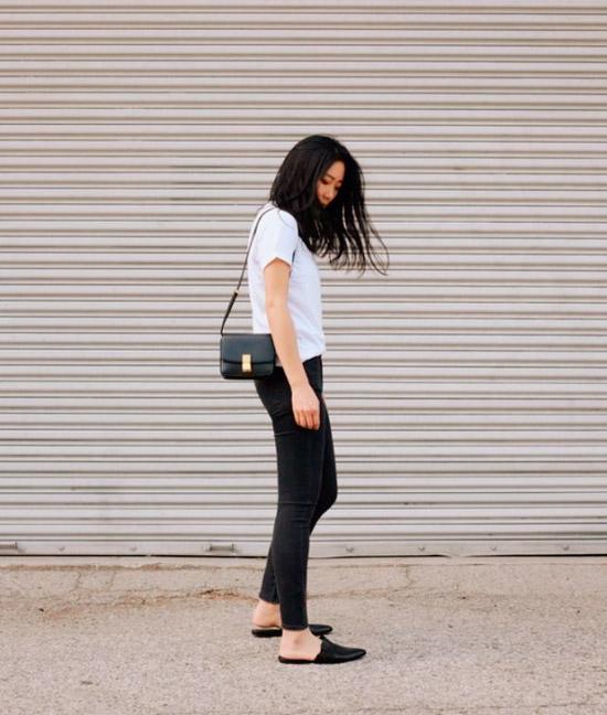 Девушка в черных джинсах скинни, белая футболка и черные лоферы