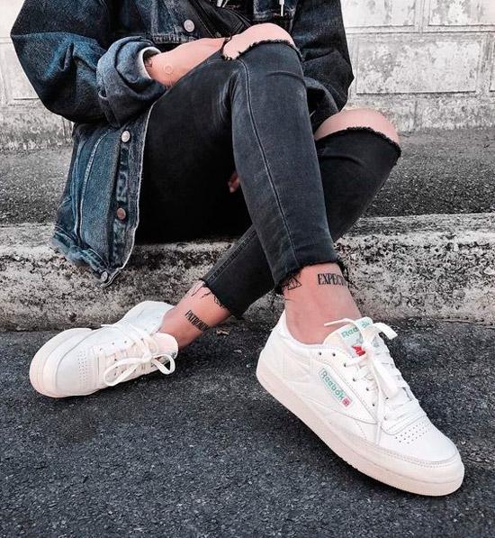 Девушка в черных рванных джинсах, джинсовая куртка и белые кеды