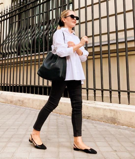 Девушка в черных узких джинсах, белая рубашка оверсайз и черные балетки