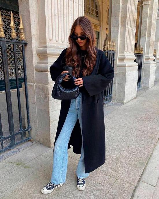 Девушка в голубых джинсах клеш, черное длинное пальто, мягкая сумочка и кеды