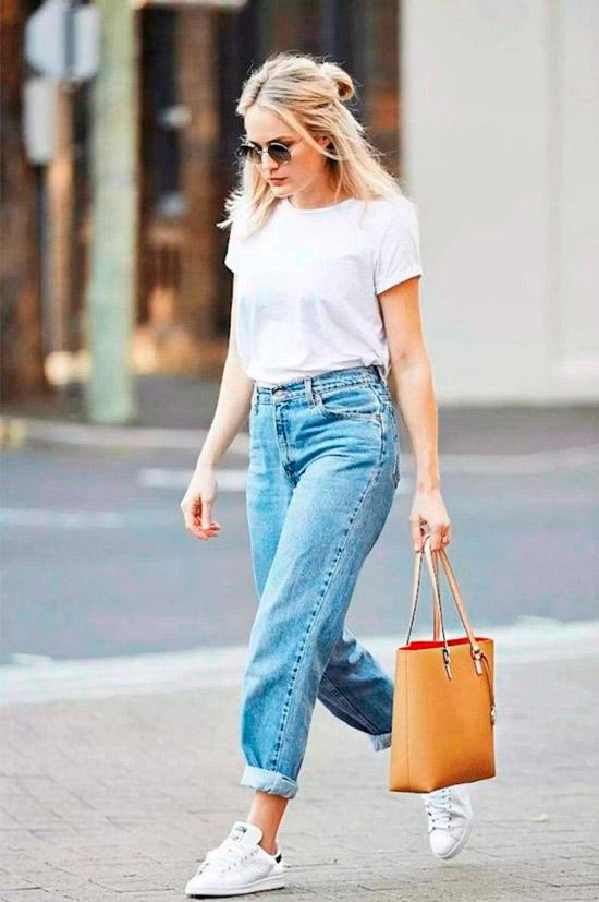 Девушка в голубых прямых джинсах, простая белая футболка, кеды и бежевая сумочка