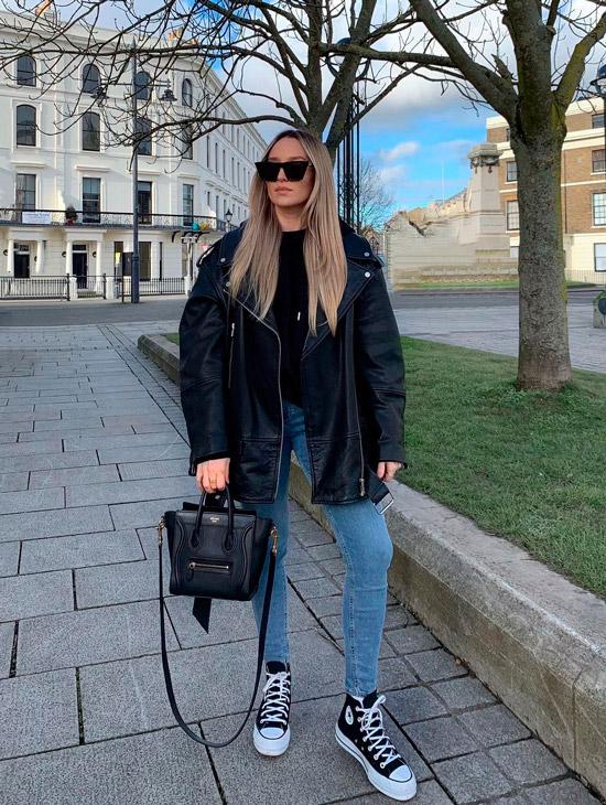 Девушка в голубых узких джинсах, кожанная куртка оверсайз, образ дополняют классические кеды и черная сумка