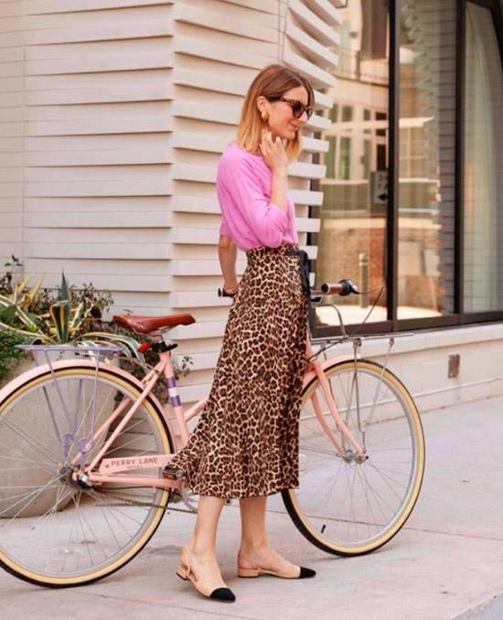 Девушка в легкой леопардовой юбке, розовая кофта и бежевые балетки с черным носом