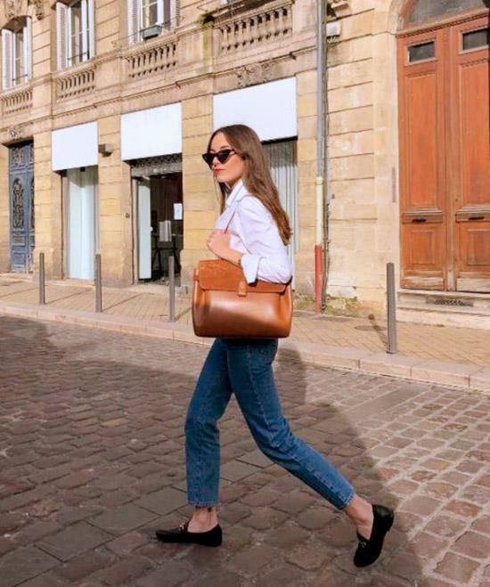 Девушка в простых джинсах, белая рубашка и черные лоферы завершают стильный образ