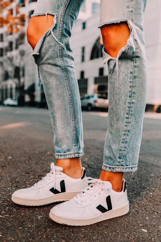 Девушка в рванных джинсах, белые кеды с черными полосами