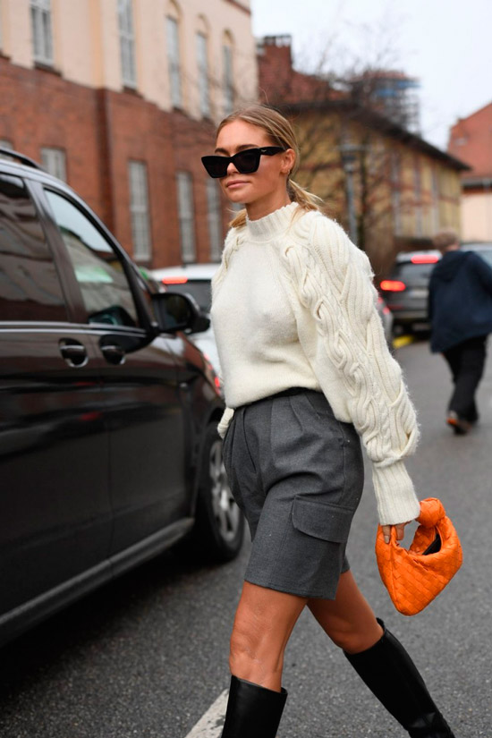 Девушка в серых шортах бермудах, теплый свитер молочного цвета и оранжевая мягкая сумочка