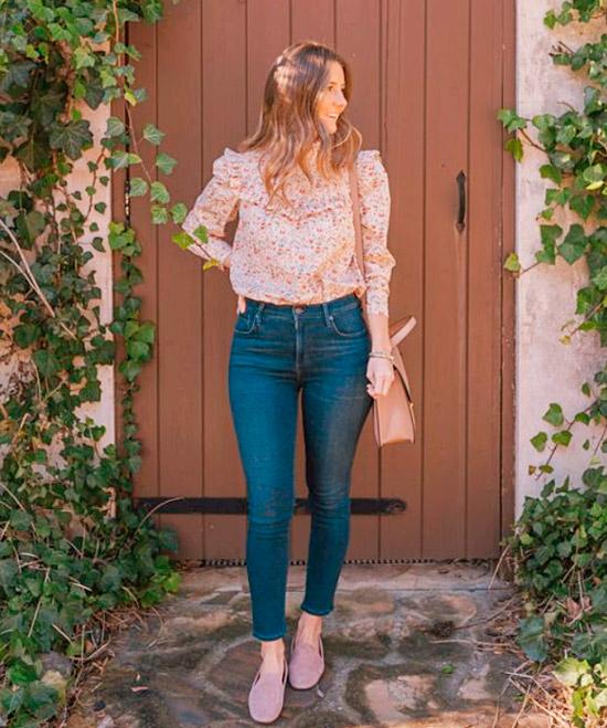 Девушка в синих облегающих джинсах, блузка с цветочным принтом и розовые замшевые лоферы