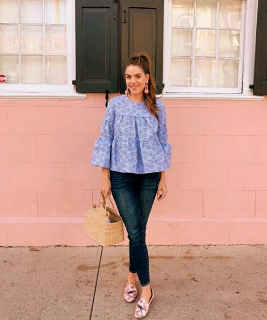 Девушка в синих облегающих джинсах, свободная голубая рубашка и лоферы с цветочным узором