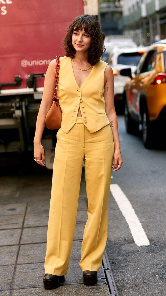 Девушка в свободных желтых брюках, желтый жилет и закрытые туфли на высокой платформе