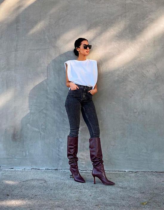 Девушка в темных узких джинсах, белая просторная футболка и высокие сапоги на шпильке