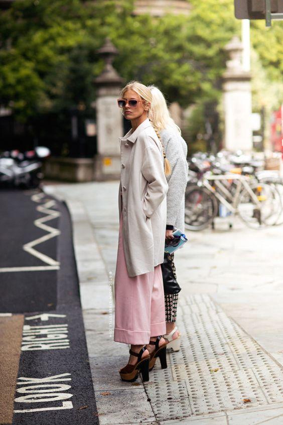 Девушка в укороченных розовых брюках, бежевый плащ и коричневые босоножки на платформе
