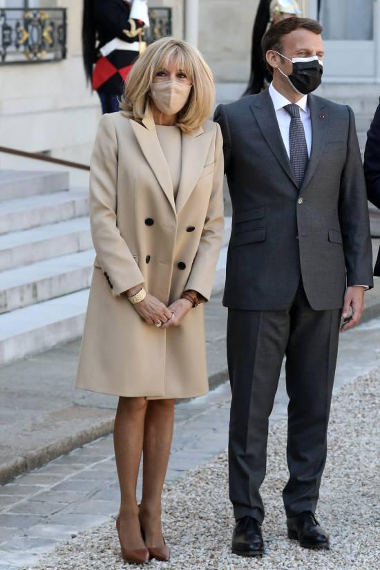 Брижит Макрон в бежевом пальто и туфлях