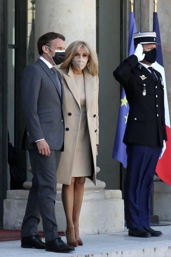 Брижит Макрон в бежевом пальто и платье футляре