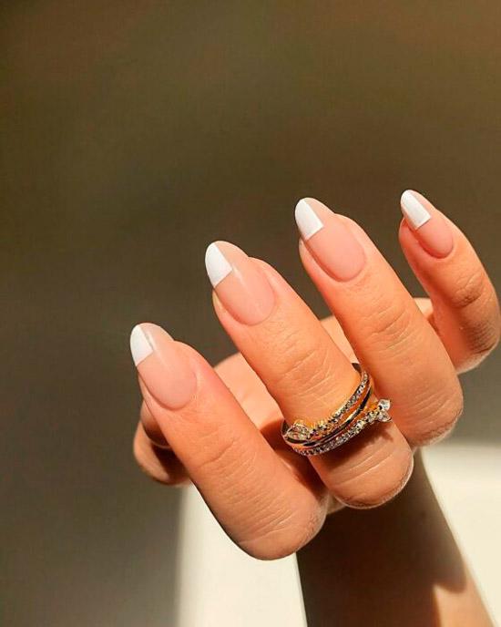 Простой бежевый маникюр с белым необычным френчем на овальных ногтях средней длины
