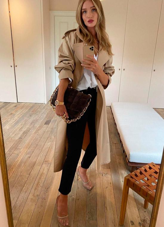 Роузи Хантингтон в черных узких джинсах, рубашка оверсайз, классический плащ и сумочка с ремешком на цепочке